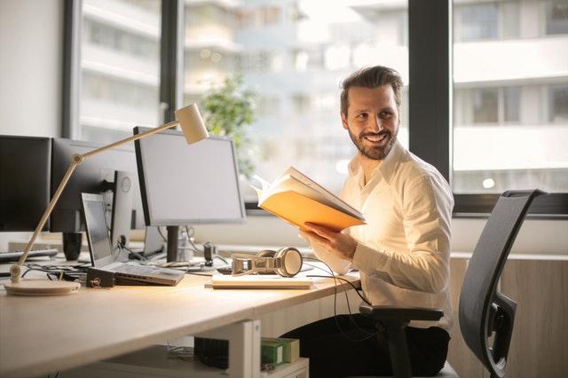 mladý muž v bílé košili, sedí za stolem